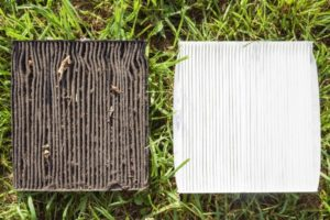 dirty and clean vehicle air filters on the green grass